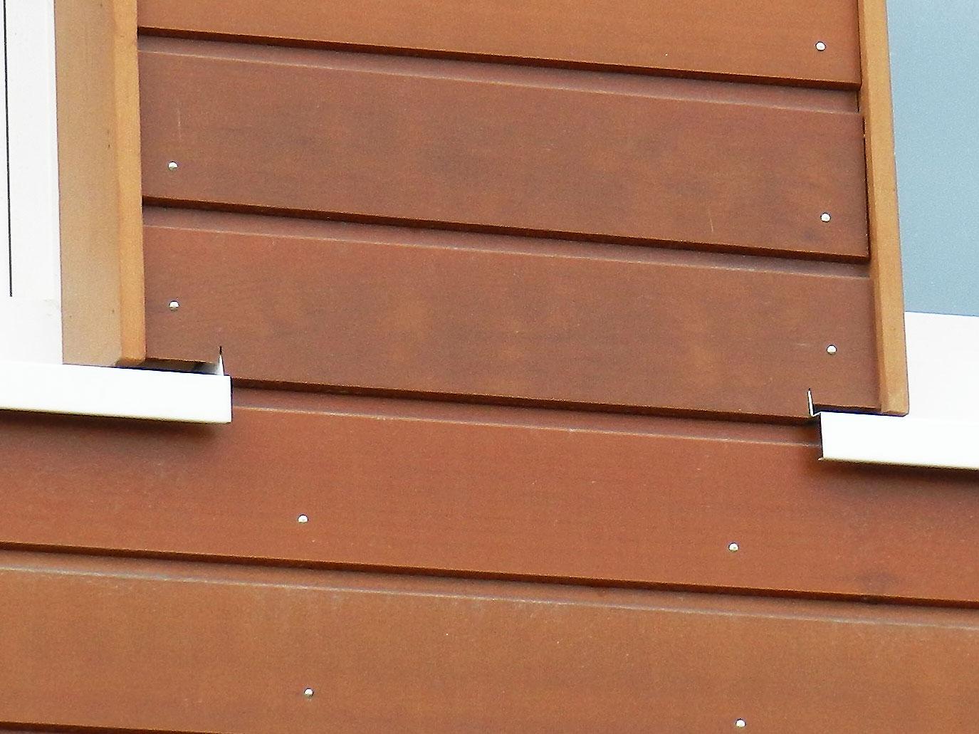witte aluminium waterslag doorgetrokken in houten gevel, ingezoomd